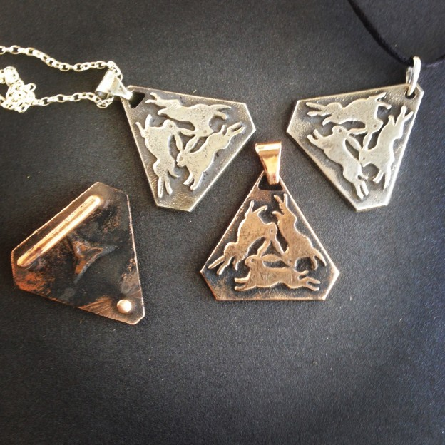 Three Hares, Sandcast silver and bronze, pendants and belt buckle